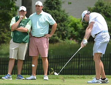 Michael McDermott (right) tees off while Jeff Osberg<br>(second left) looks on