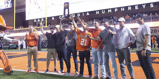 Showing off last year's national championship trophy (OkSt Athletics photo)